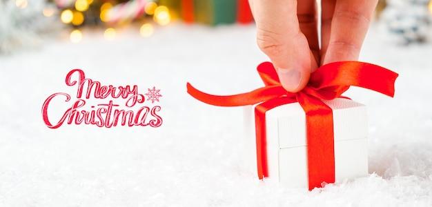С рождеством христовым поздравительная открытка с мужской рукой, держащей подарочную коробку с красной лентой на снегу и размытыми огнями