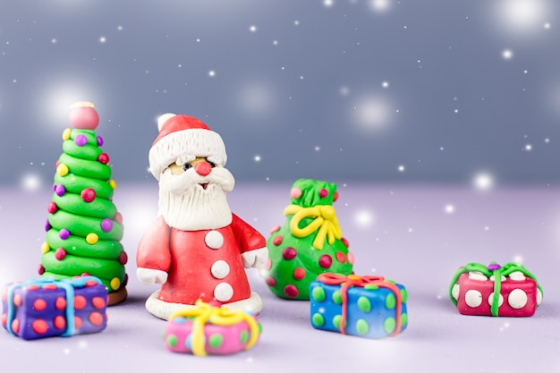 Merry christmas greeting card with decorations. santa claus, christmas tree and presents close up on neutral background