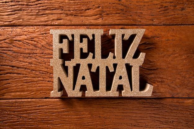 木製の背景にメリークリスマスの挨拶のメッセージ。ポルトガル語で書かれたメリークリスマス。フェリス出生。