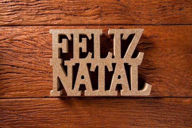 Merry christmas greeting message on wooden background. merry christmas written in portuguese. feliz natal.