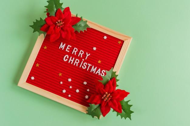 С рождеством христовым поздравительная открытка в стиле минимализма. доска для писем с приветствиями и красными цветами пиосентия на зеленом фоне.