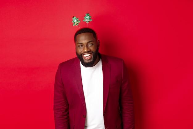メリークリスマス。ブレザーとパーティーのヘッドバンドでハンサムなアフリカ系アメリカ人の男、新年を祝って、カメラ、赤い背景で幸せに笑っています。