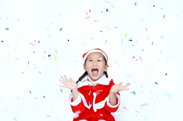 Merry christmas happy child girl in santa costume dress with colorful confetti on white ba