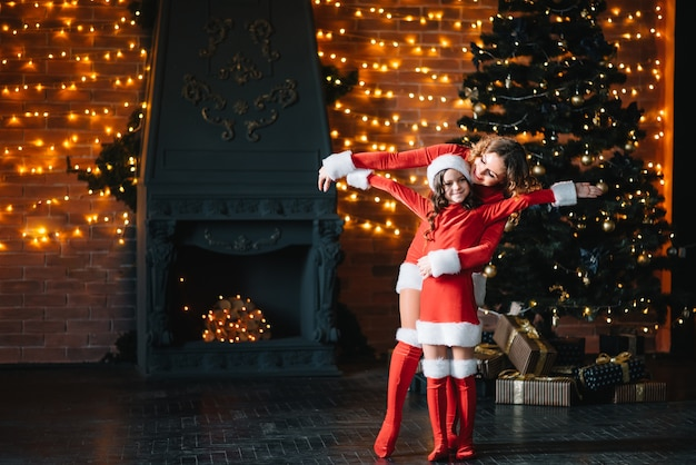 Merry christmas and happy holidays! beautiful mother with little daughter in christmas costumes spend time together near the christmas tree.