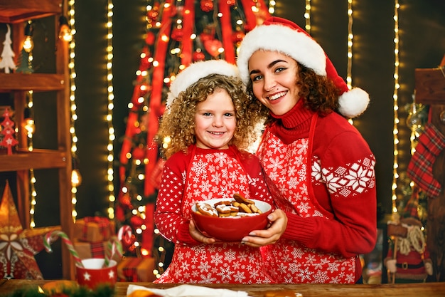 Merry christmas and happy holidays. cheerful cute curly little girl and her older sister in santas hats cooking christmas cookies.