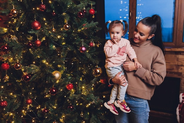 Merry christmas and happy holidays cheerful mom and her cute daughter girl exchanging gifts. parent and little child having fun near christmas tree indoors. loving family with presents in room.
