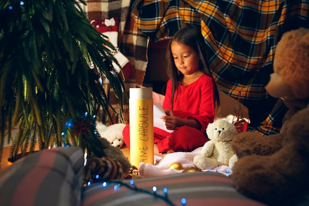 Merry christmas and happy holidays. cute little child girl writes the letter to santa claus near christmas tree at home indoor. holiday, childhood, winter, celebration concept