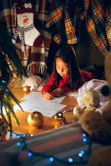 Merry christmas and happy holidays. cute little child girl writes a letter to santa claus near christmas tree