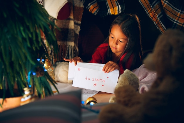 Merry christmas and happy holidays. cute little child girl writes the letter to santa claus near christmas tree
