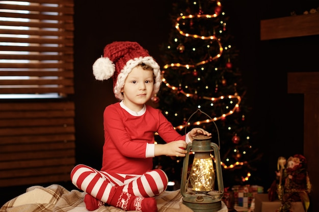 Merry christmas and happy holidays a little boy is sitting with a lantern at the christmas tree new year, elf