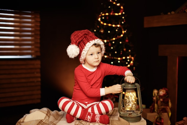 Merry christmas and happy holidays a little boy is sitting with a lantern at the christmas tree new year, elf.