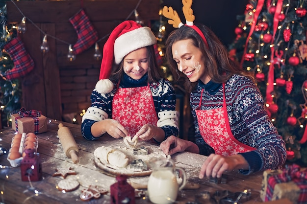 Merry christmas and happy holidays, mother and daughter cooking christmas cookies.