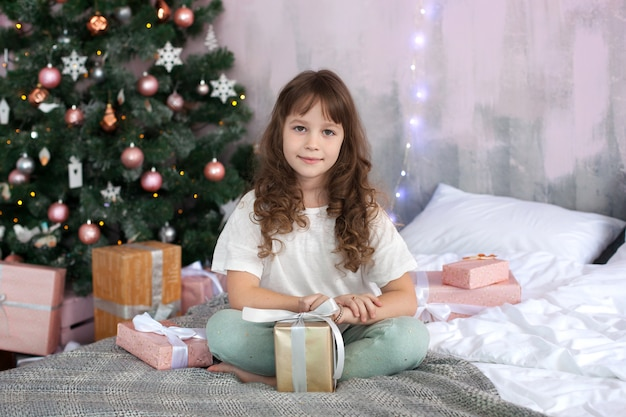 Merry christmas and happy holidays! new year 2020! close-up portrait of a little girl in a christmas morning
