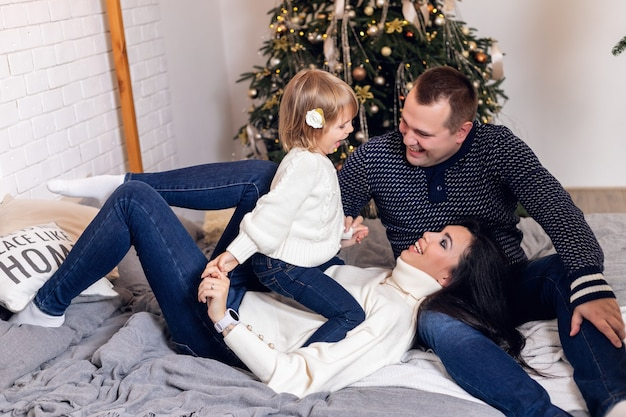 Merry christmas and happy holidays parents and young baby daughter girl have fun and play together near the christmas tree indoors.