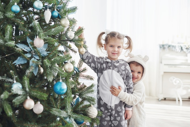 Merry christmas and happy holidays! young girls helping decorating the christmas tree, holding some christmas baubles in her hand