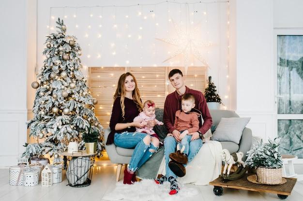 メリークリスマス。幸せな母の父と屋内のクリスマスツリーの近くの子供たち。家族で一緒に楽しんでいます。