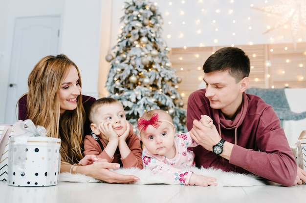 Счастливого рождества счастливая мать, отец и дети с волшебным подарком возле елки в помещении