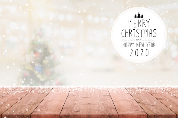 Merry christmas and happy new year 2020 on empty wood table top on blur bokeh christmas tree background with snowfall.