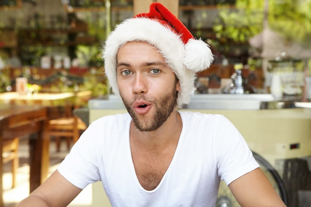 Merry christmas and happy new year! attractive young bearded man wearing red hat with white fur relaxing indoors, pretending to be santa claus, laughing and opening his mouth as if saying: ho ho ho!