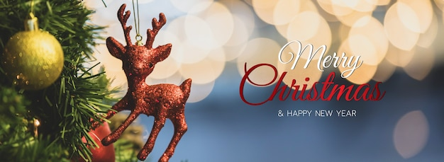 Merry christmas and happy new year banner for head or cover of social media website or fan page decorative.      red reindeer ornament doll hanging on a fake pine tree and blur light bokeh background.