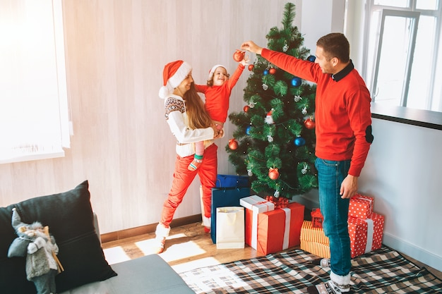 Merry christmas and happy new year. beautiful and bright picture of young family standing at christmas tree. man holds red toy and smiles. child reaches to it with interest.