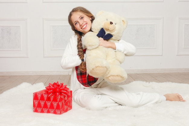 Merry christmas and happy new year beautiful happy child girl in pajamas waiting for a miracle at home with christmas tree. little smiling girl with christmas gift box. holiday and people concept.