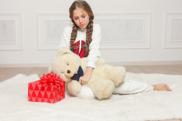 Merry christmas and happy new year beautiful happy child girl in pajamas waiting for a miracle at home with christmas tree. little smiling girl with christmas gift box. holiday and people concept. Premium Photo
