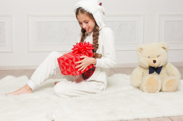 Merry christmas and happy new year beautiful happy child girl in pajamas waiting for a miracle at home with christmas tree
