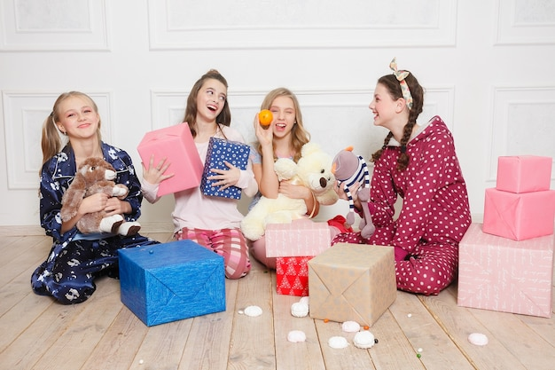 Merry christmas and happy new year beautiful happy four child girl in pajamas waiting for a miracle at home with christmas tree. little smiling girl with christmas gift box. holiday, people concept. Premium Photo