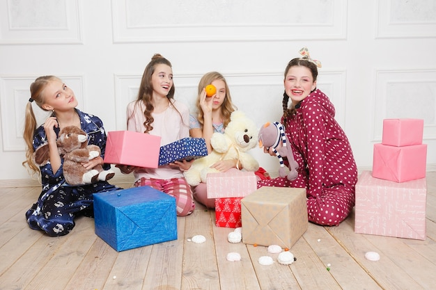 Merry christmas and happy new year beautiful happy four child girl in pajamas waiting for a miracle at home with christmas tree. little smiling girl with christmas gift box. holiday, people concept.