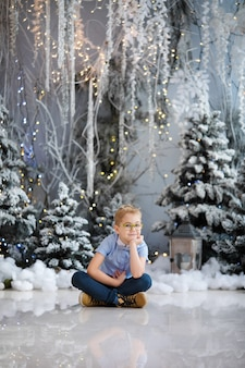 Merry christmas and happy new year! charming little boy is sitting at home
