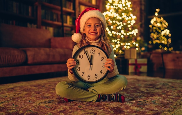 Merry christmas and happy new year! charming little girl is sitting at home with clock in hands, smiling  five minutes till the new year.