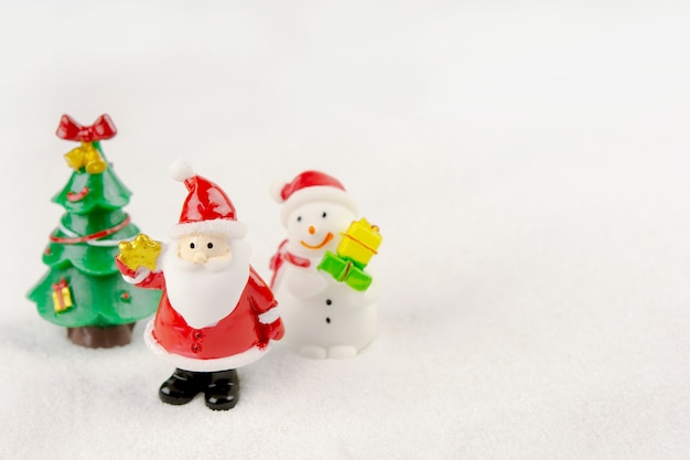 Merry christmas and happy new year concept. cute santa claus,  snowman figure and tree on snow with copy space