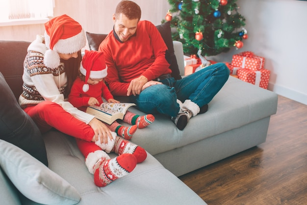 Merry christmas and happy new year. family sitting together on sofa. small girl is in between her parents. she holds and looks at book with pictures. man looks t it and smile. they are happy.
