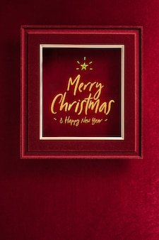 Merry christmas and happy new year glowing with star in picture frame on velvet red felt fabric wall.