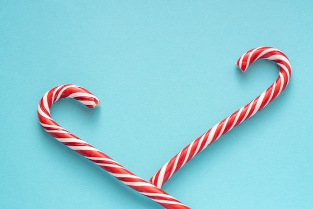 Merry christmas and happy new year greeting card. two candy canes on blue background with copyspace for your text.