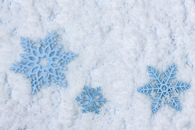 Merry christmas and happy new year greeting card with blue wooden snowflakes on snow background with copy space. flat lay. top view.