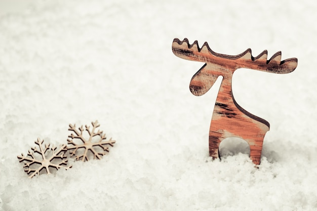 Merry christmas and happy new year greeting card with small wooden figure of deer on snow background with copy space.