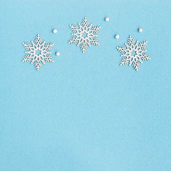 Merry christmas and happy new year greeting card with wooden snowflakes on blue background