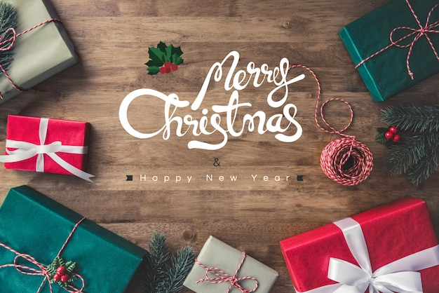Merry christmas and happy new year greeting text on a wooden table background with gift boxes