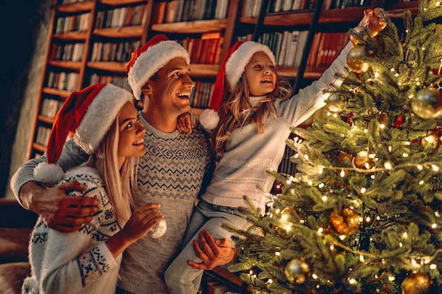 Merry christmas and happy new year! happy family celebrating winter holiday at home. mom, dad and daughter decorating new year tree.