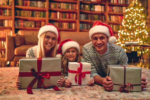Merry christmas and happy new year! happy family is waiting for the new year in santa claus hats lie on the floor and hold their gift boxes.