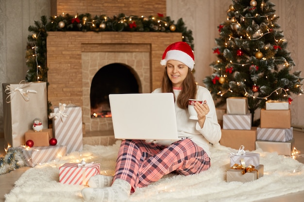 Merry christmas and happy new year, smiling woman meeting together with somebody online via video calling on laptop, drinking coffee or tea while sitting on floor near fireplace.