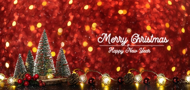 Merry christmas and happy new year text over xmas tree on red glitter sparkling string lights