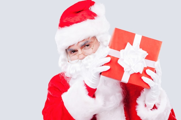Merry christmas and happy new year! traditional santa claus holding gift box and looking at camera while standing against grey background