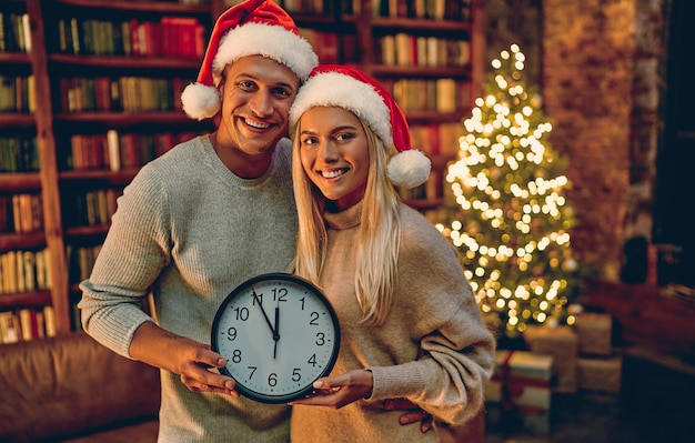 Merry christmas and happy new year! young couple  with clock in their hands smiling  five minutes till the new year.