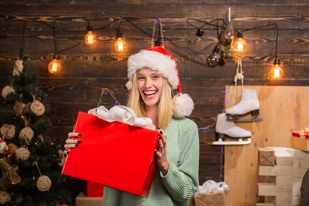 Merry christmas and happy new year young woman with christmas present boxes in front of christmas tr...