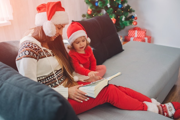 Merry christmas and happy new year. young woman with red hat sit on sofa with daughter. she holds book on her lap. woman looks down and smiles. small girl is calm. she looks at book too.
