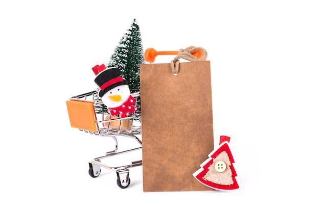 メリークリスマスホリデー!白い壁のコピースペースで隔離の小さなプッシュカート内の楽しい面白いファンキーなサンタ雪だるま赤と緑の木のクローズアップ