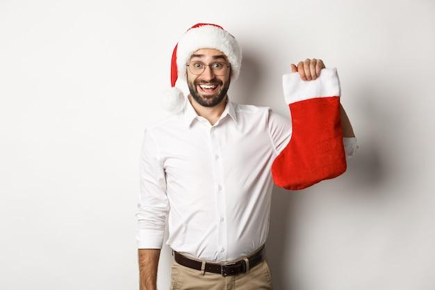 С рождеством христовым, концепция праздников. взволнованный бородатый парень в новогодней шапке держит рождественский носок и улыбается, празднуя новый год